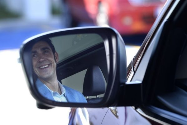 Smiling nissan driver in wingmirror