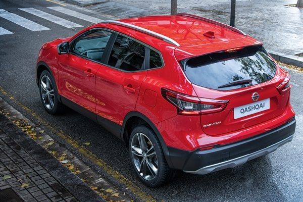 Red Nissan Qashqai driving on the road