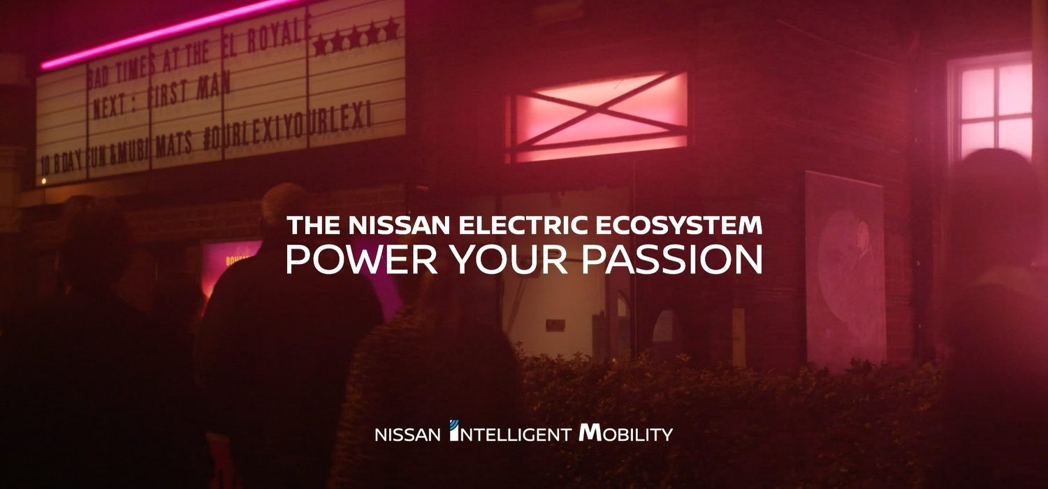 "Text reading ""electric vehicle leadership, power your passion, nissan intelligent mobility"" over crowd going in to a cinema"
