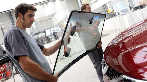 Two nissan engineers fitting a windscreen onto a vehicle