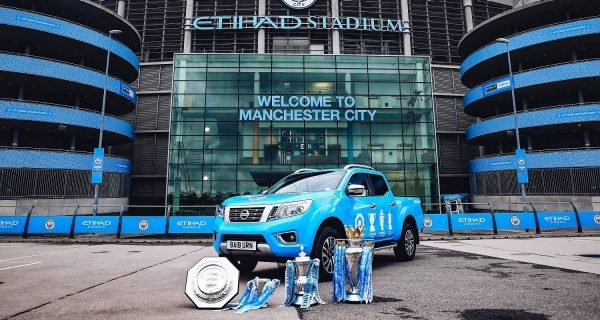 Blue nissan navara parked in front of manchester city stadium, with 4 trophy cups