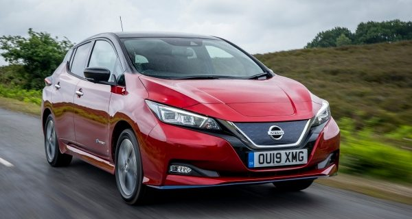 The electric nissan leaf driving down a green country road