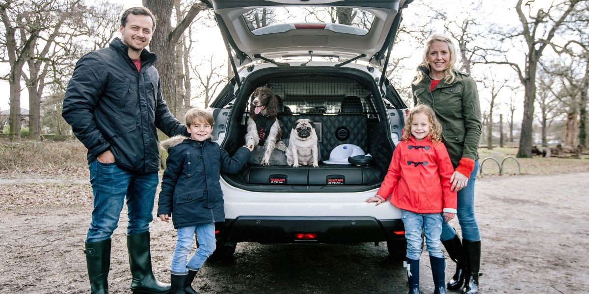 Family with children and dogs infront of X-Trail