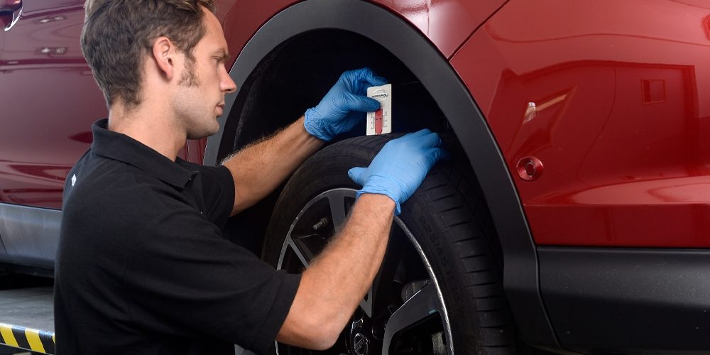 A man measuring tyre of Nissan car