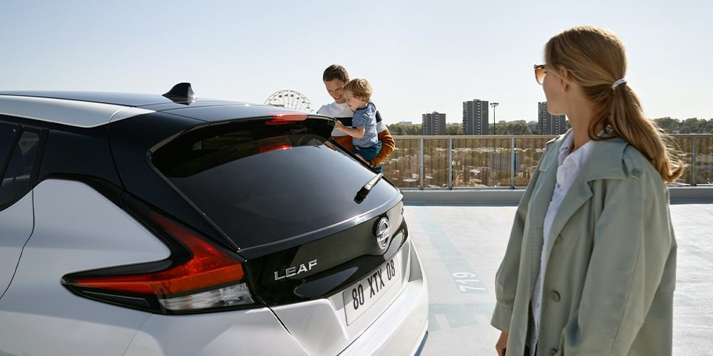 Nissan leaf, back view of the car, with a women standing watching the London skyline and a man carrying his child