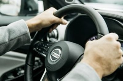 A person holding a Nissan Steering Wheel
