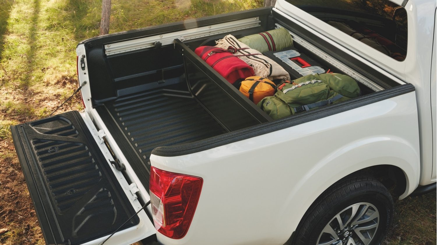 White nissan navara with bed divider in carriage