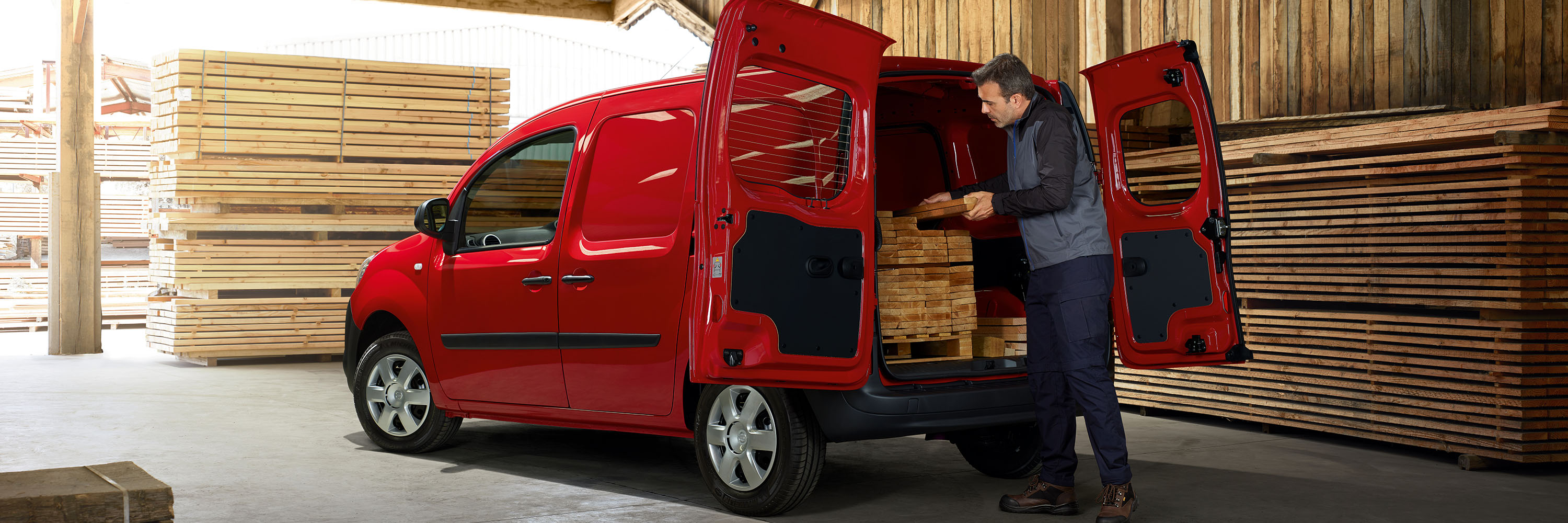Nissan NV250 in a sawmill with a man loading the cargo with wood
