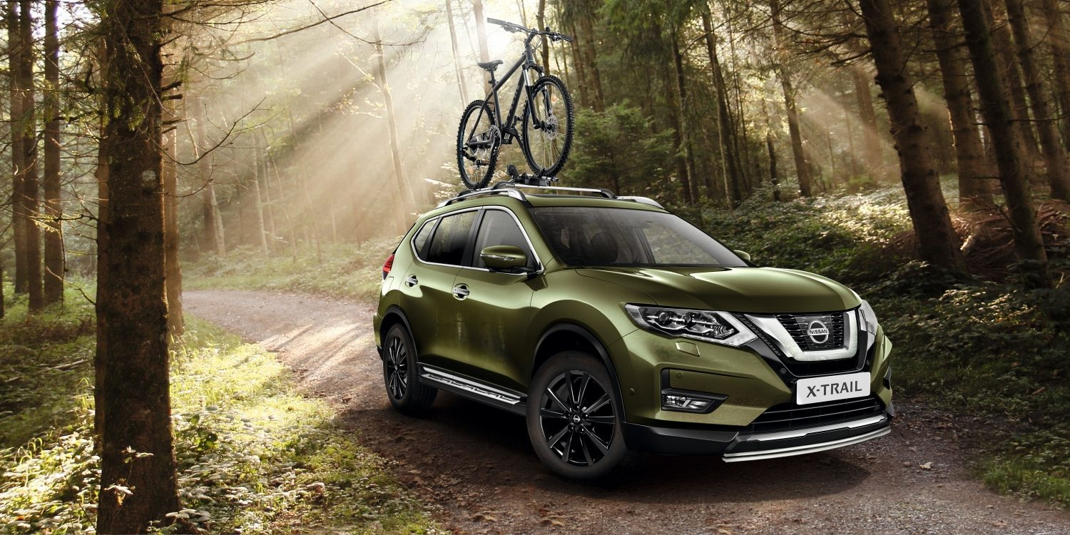 X-Trail accesorised in the forest with bike carrier on the roof