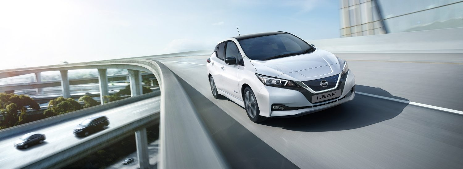 New Nissan LEAF shown from the front driving on a highway overpass