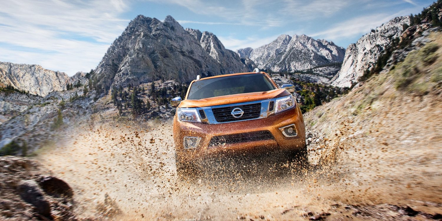 Nissan Navara kicking up dirt on off-road mountain trail