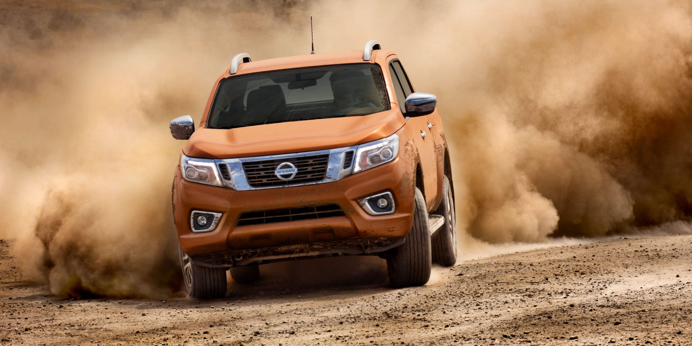 Nissan Navara kicking up dust on dirt road