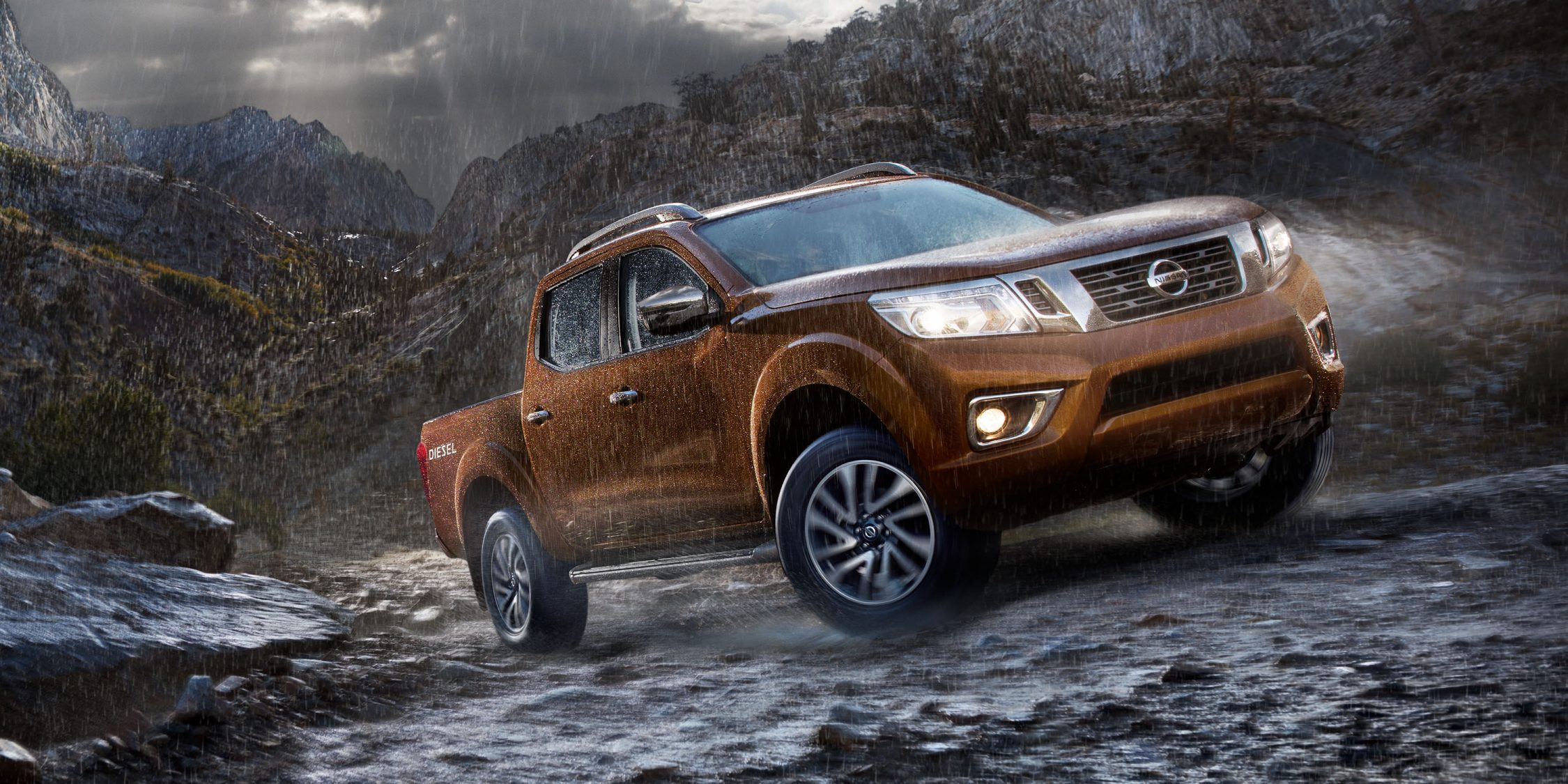 Nissan Navara driving up mountain trail in rain