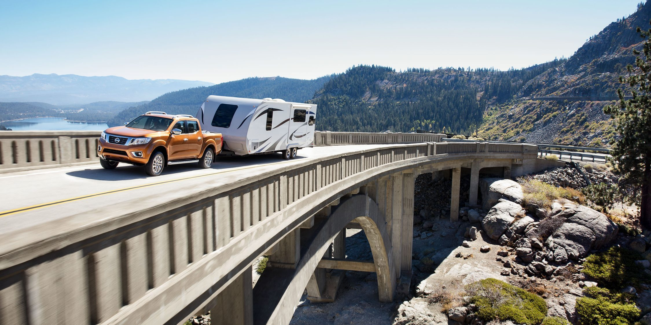Nissan Navara towing trailer over scenic bridge