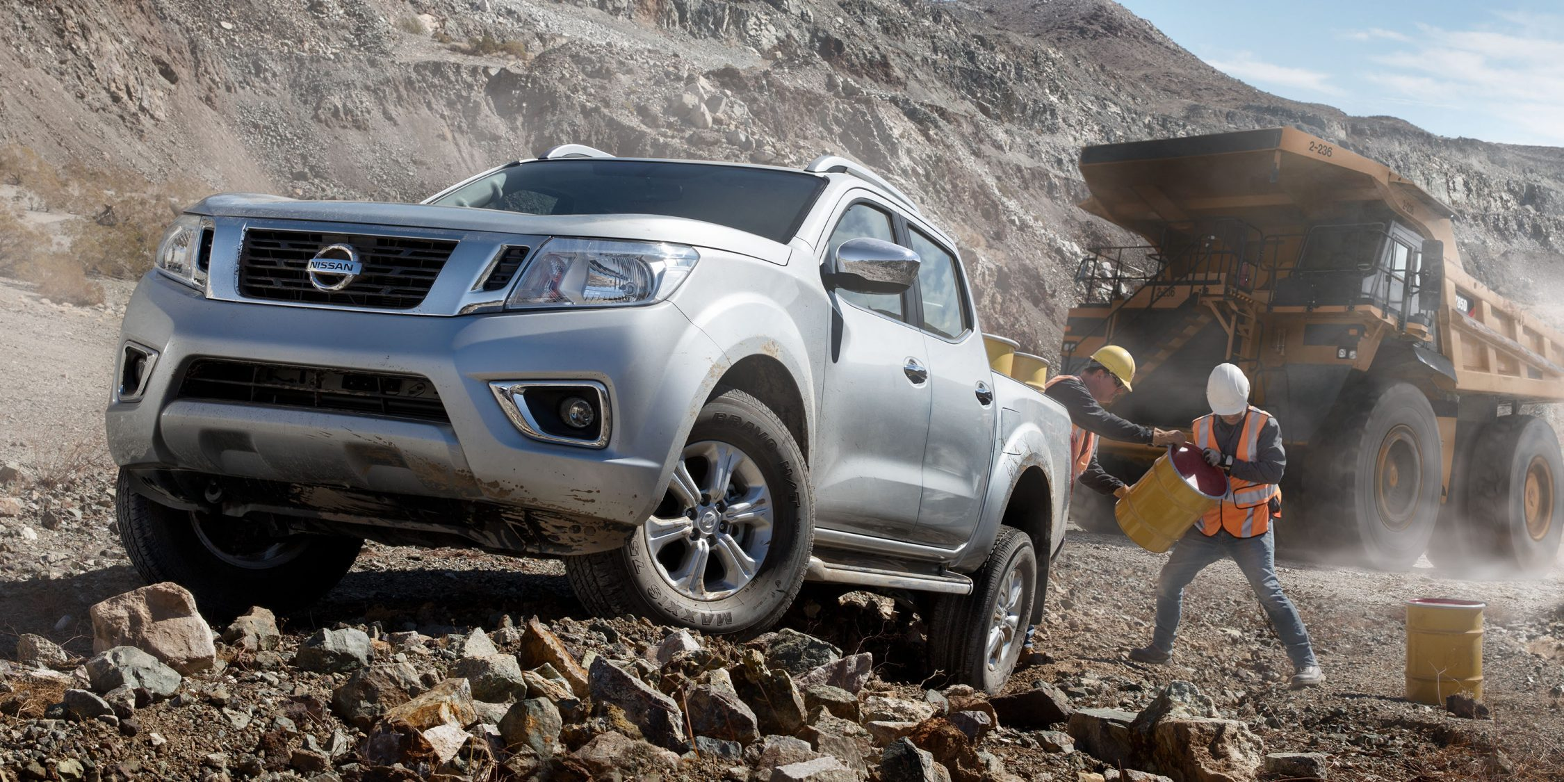 Nissan Navara parked on rocky terrain with workers and large equipment in the background