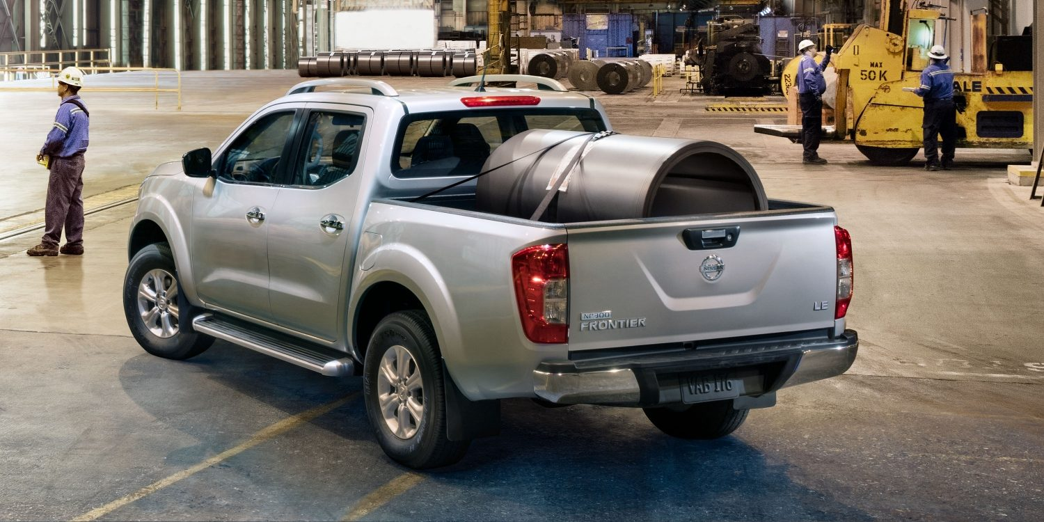 Nissan Navara parked in factory with large pipe secured in cargo bed