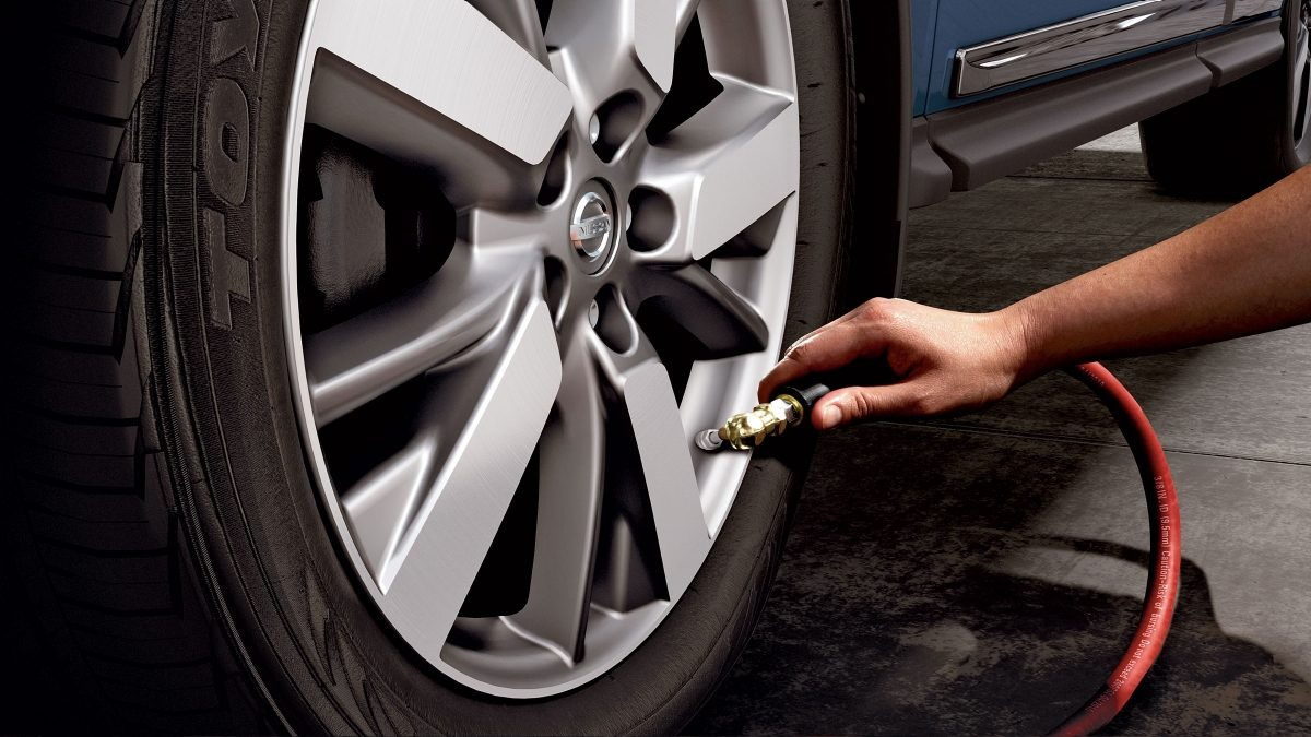 Nissan Pathfinder TPMS with Easy-Fill Tyre Alert with person filling up tyre