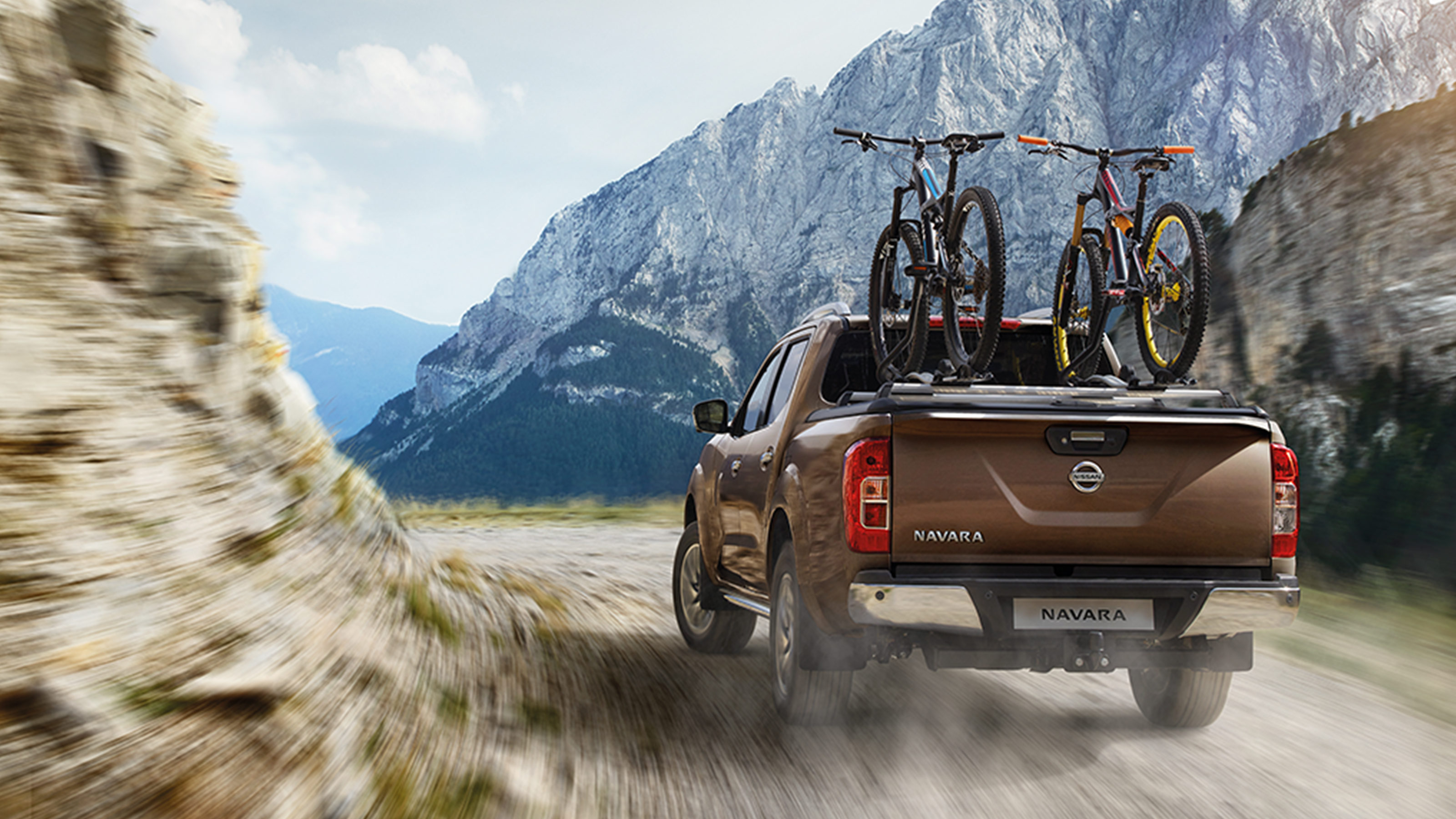 Nissan Navara rear driving shot with bikes on the bed