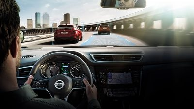 Inside view of a Nissan car with a man driving with Nissan Intelligent Mobility