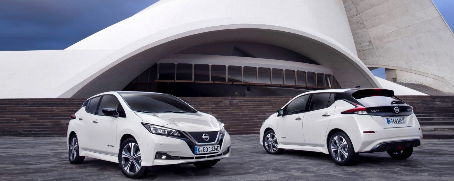 Two New Nissan LEAFs in 3/4 front and 3/4 rear parked in front of a modern building