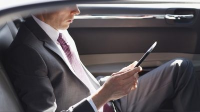 Business man watching his phone in the second row of a car