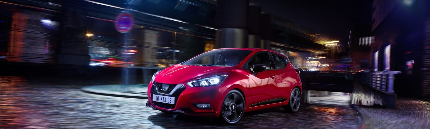 Nissan MICRA driving in city by night