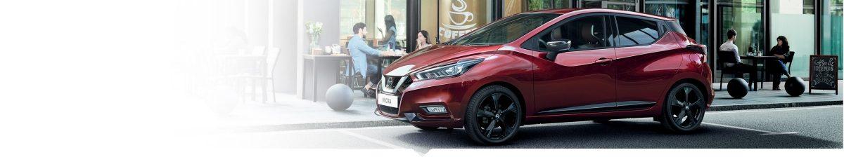 Ein NISSAN MICRA parkt an einem Bürgersteig vor einem Café