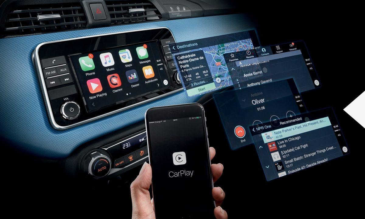 Innenansicht des NISSAN MICRA mit umherschwebenden Bildschirmen und einem Smartphone mit Apple CarPlay