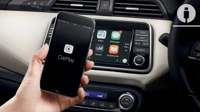 Nissan MICRA centre console with hand holding a smartphone with Apple CarPlay
