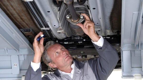Authorised repairer working on a Nissan undercarriage