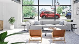 A window view of Nissan shop with comfortable sofa, chairs and table. Outside the window is a red Nissan car