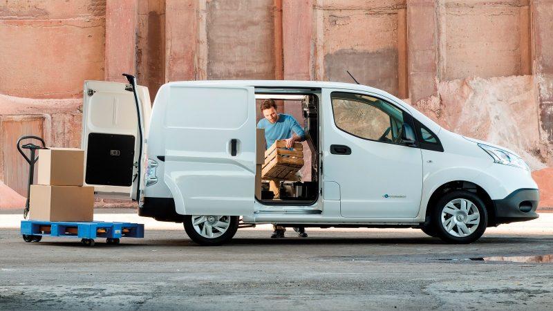 Profilo del nuovo Nissan e-NV200 con porte aperte e uomo che carica il veicolo