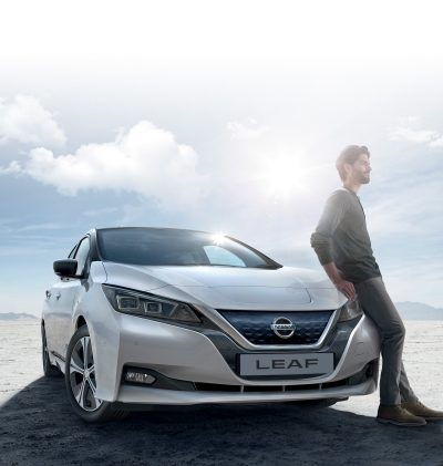 Nissan LEAF in the desert with a man sitting on the car