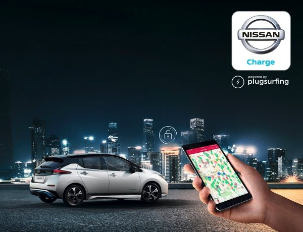 Hand holding a smartphone with Nissan Charge screen with Nissan LEAF parked with a city in the background and app logo