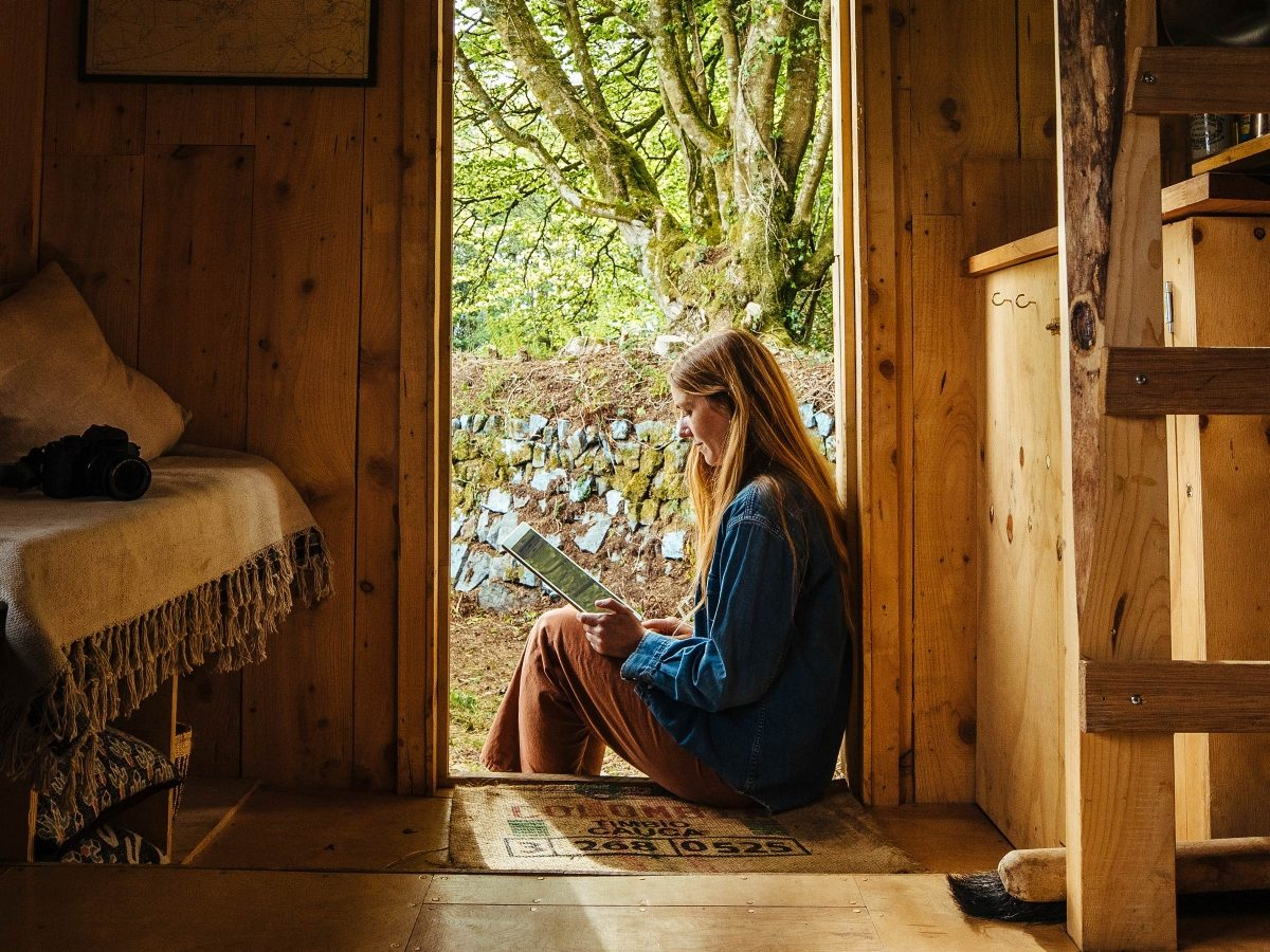 Women reading on a tablet in a cabin in the woods
