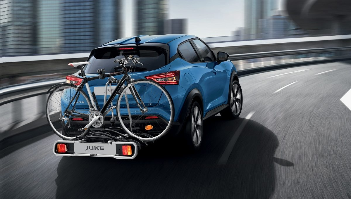 Nissan JUKE driving in a curve with a towbar mounted bike carrier