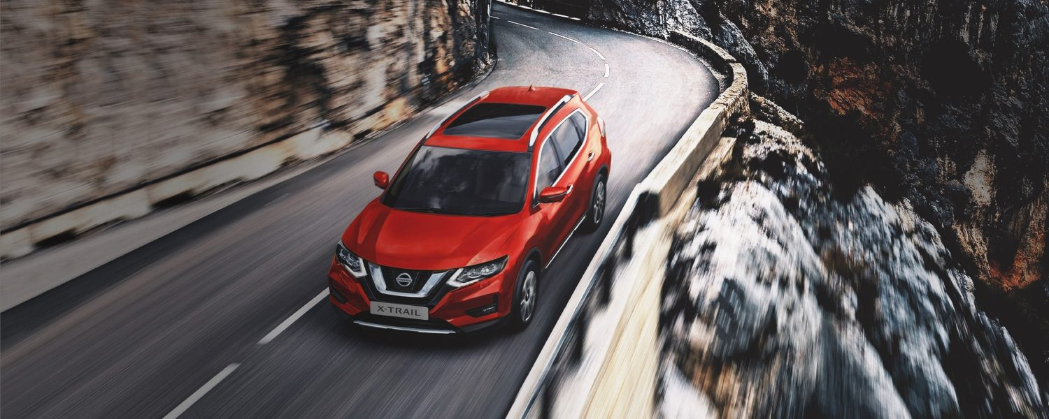 Nissan X-Trail driving on a road in the mountains