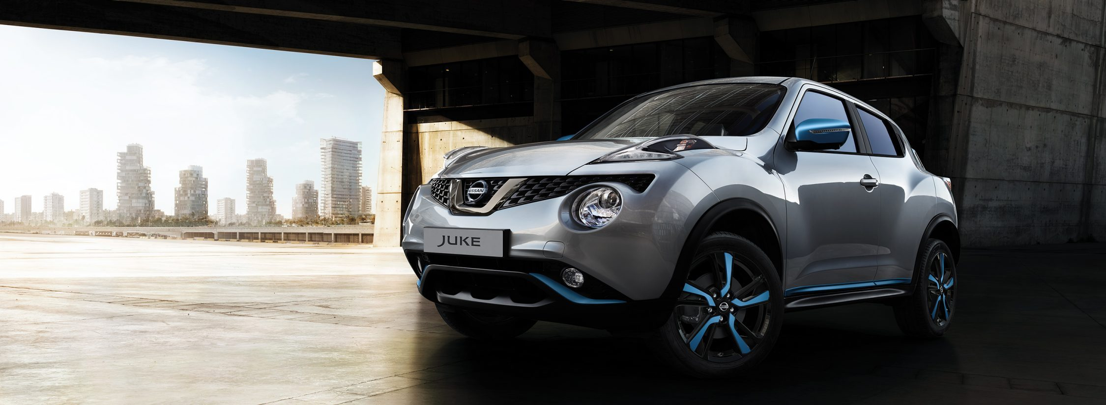 2018 Nissan JUKE 3/4 front low parked under a bridge with power blue personalisation
