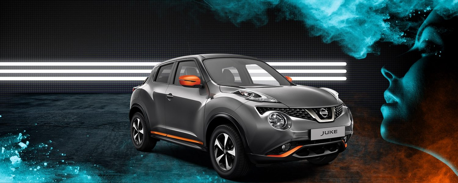 Grey Nissan JUKE with orange accents in front of a white 3-stripe LED display.