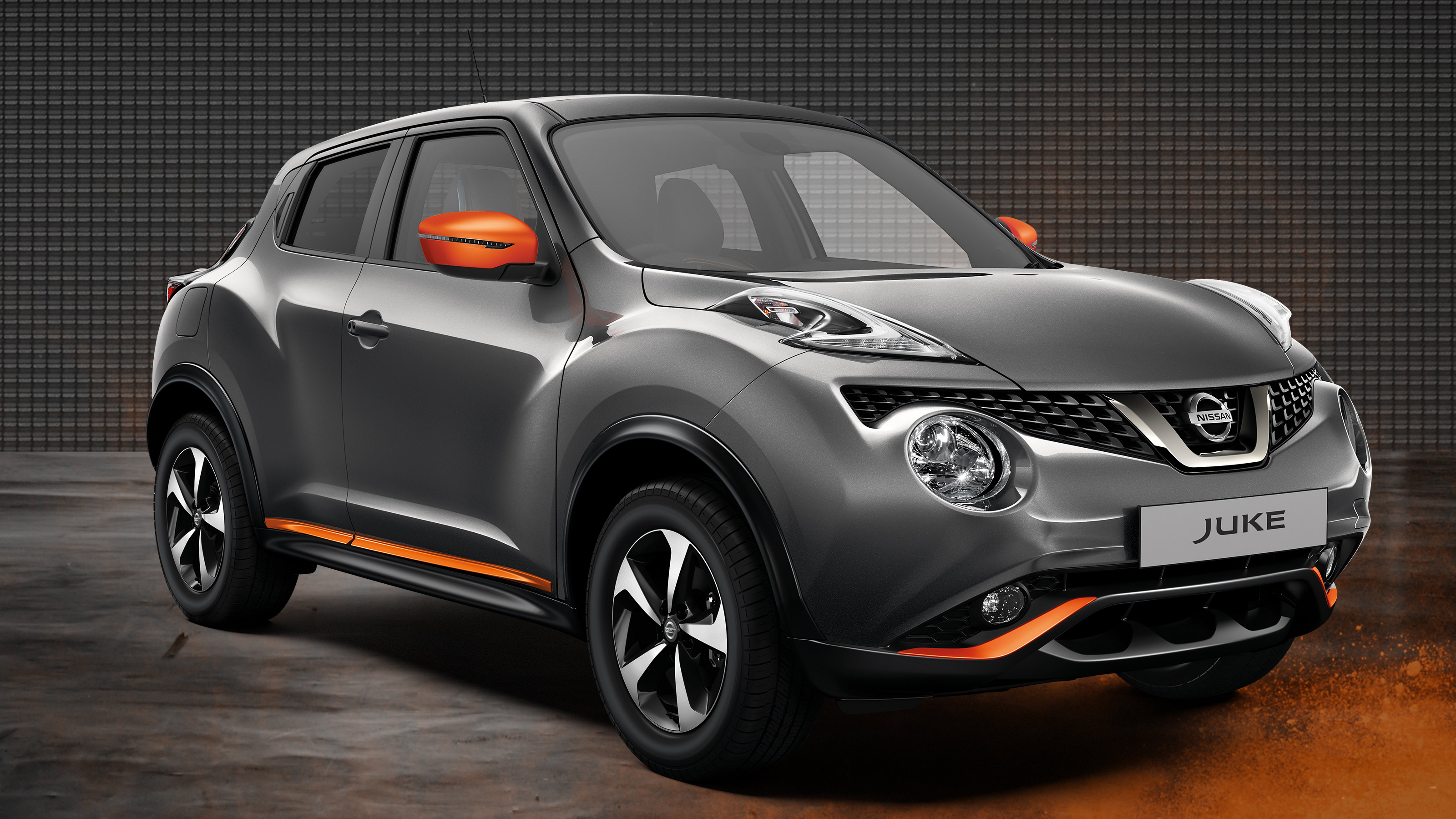 Grey Nissan JUKE with orange accents on bumpers and wing mirror.