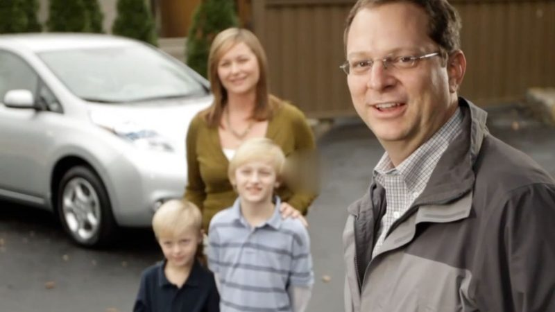 Family standing next to vehicle