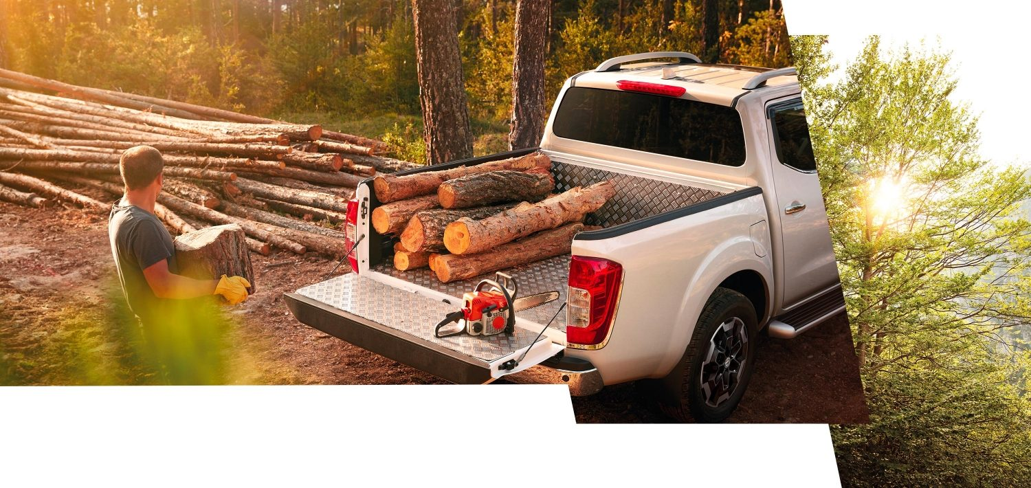 Nissan Navara in the forest showing aluminium bedliner loaded with wood logs