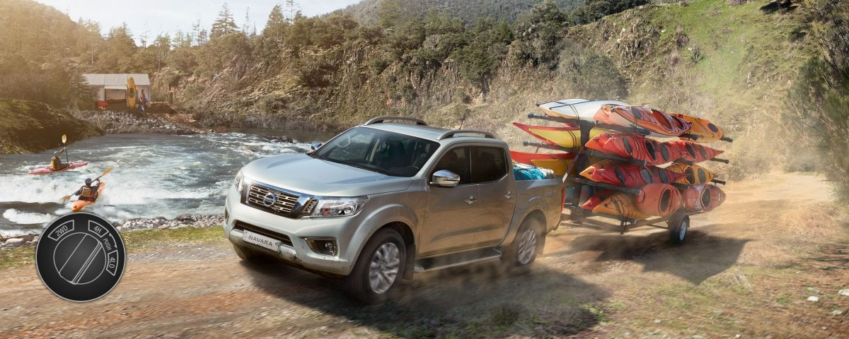 Nissan Navara towing canoes in the mountain close to a lake with 4 wheel drive high illustration