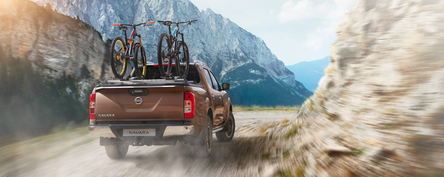 Nissan Navara rear driving shot in the mountains with bikes in the bed