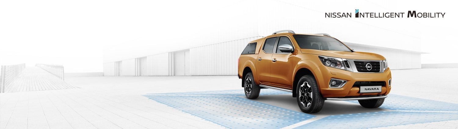 Nissan Navara 3/4 front shot parked in front of a warehouse with nissan intelligent mobility graphics around the car