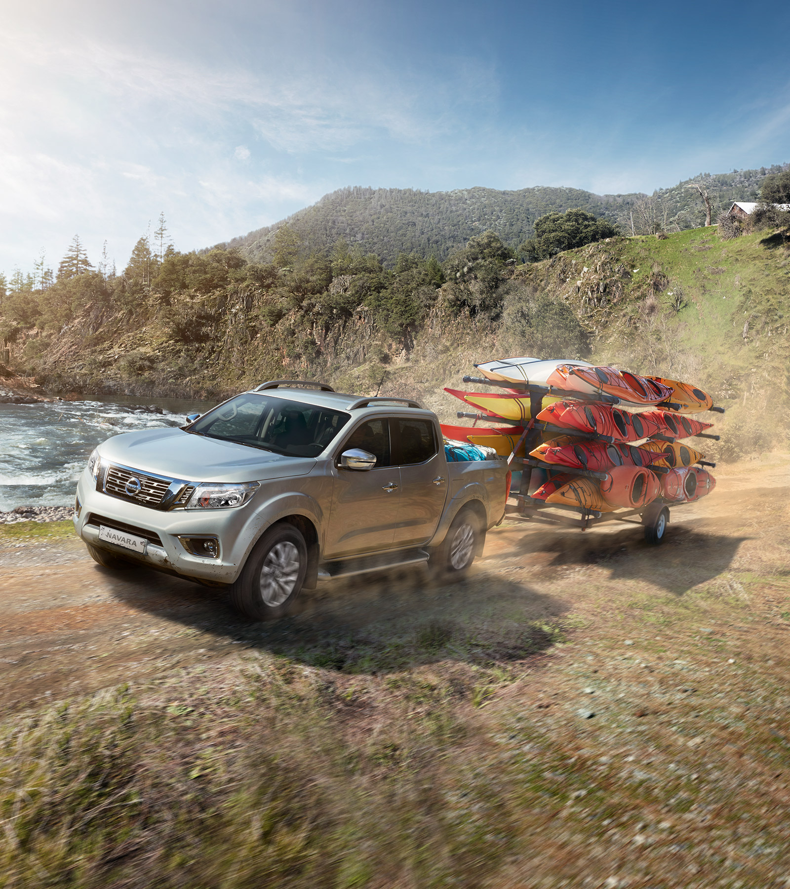Nissan Navara towing canoes in the mountain close to a lake