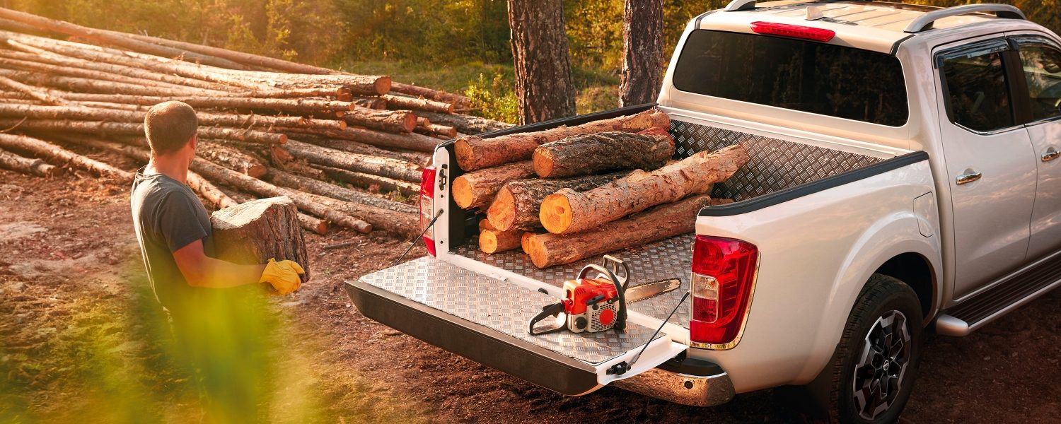 Nissan Navara 3/4 rear view with wood logs in the bed