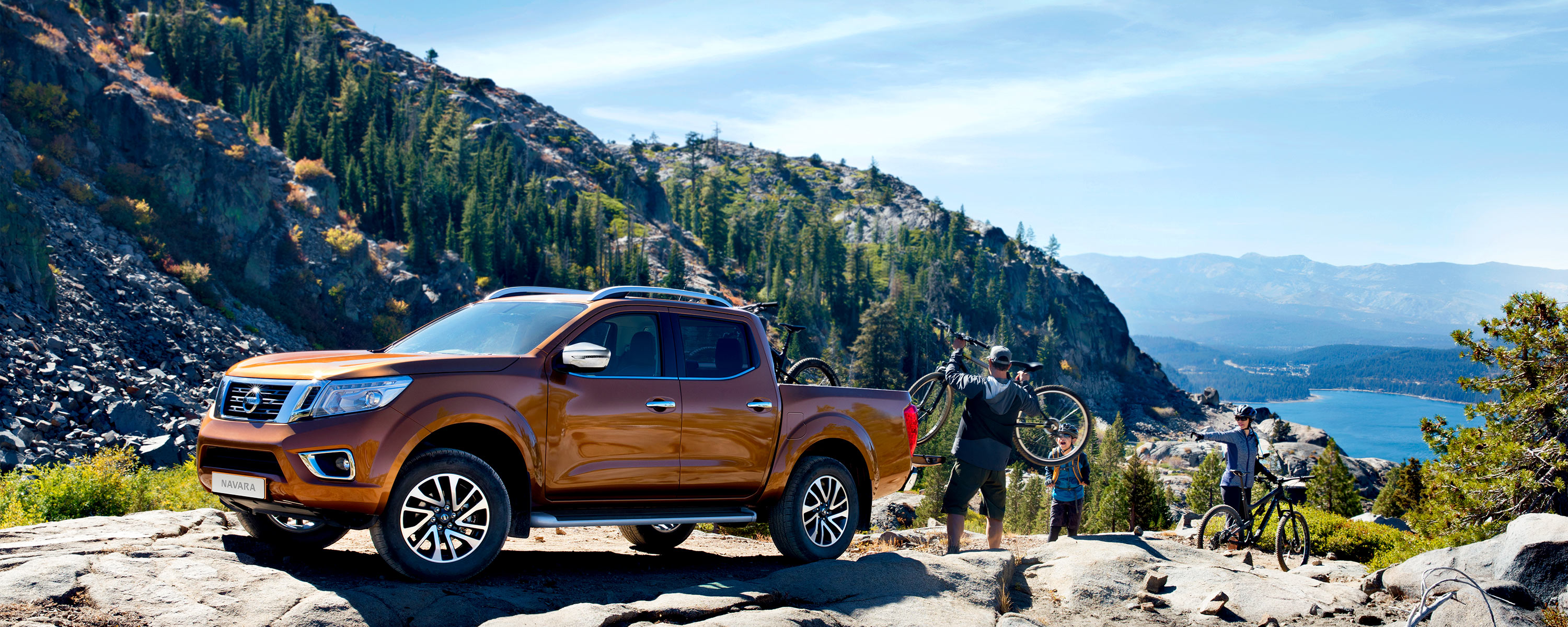 Nissan Navara beauty shot with people loading bikes in the bed