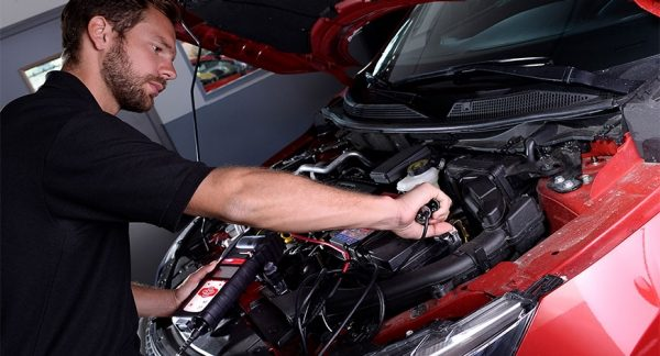 Qualified nissan engineer servicing the engine of a red nissan truck